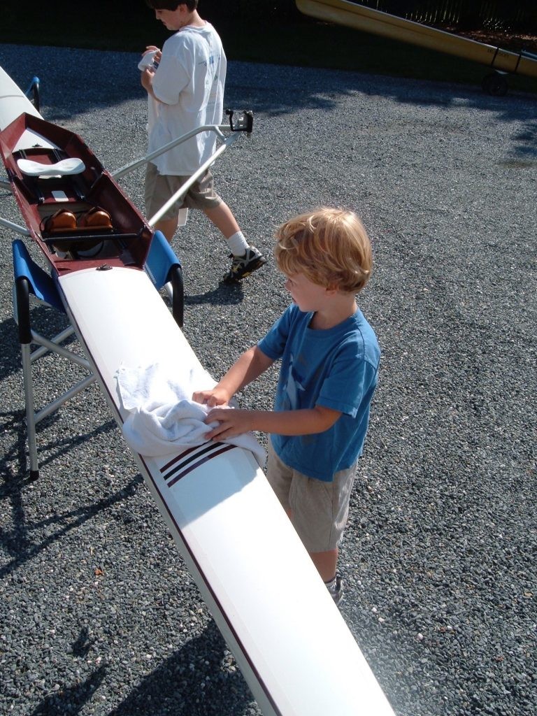This is a photograph of a boy waxing a rowing shell