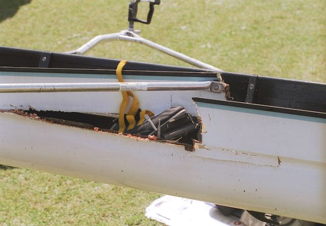 This is a photograph of a rowing shell with a broken gunwale, a boat that needs rowing equipment love.