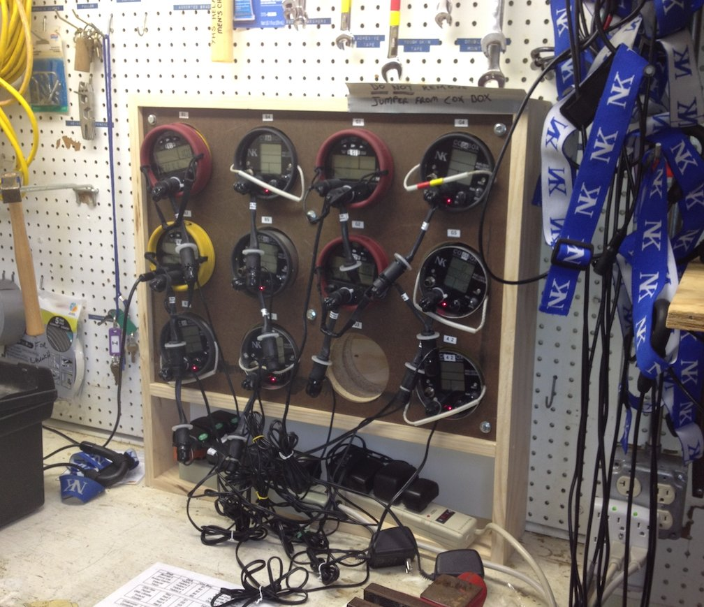 This is a picture of cox boxes organized on a workbench helping with boathouse organization